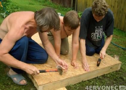 Семья в процессе строительства будки