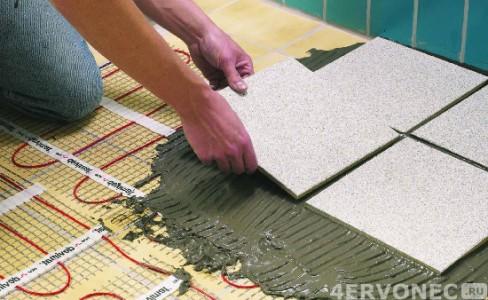Наносим клей на теплый пол и укладываем плитку
