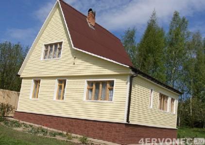 Фото дома с обшивкой светлым сайдингом и цоколем под камень