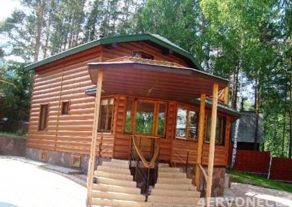 Дом с зеленой крышей, облицованный металлическим блок-хаусом