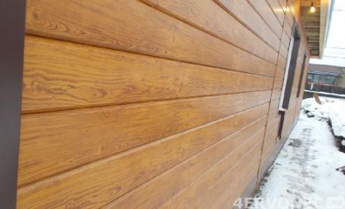 Дом с обшивкой металлическим сайдингом под древесину