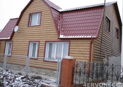Фото дома с облицовкой сайдингом под бревно и каменным цоколем