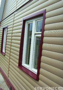 Фото дома с виниловым сайдингом под бревно и контрастной отделкой окон